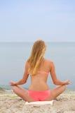 Muchacha de Eautiful en el bikini que sienta y que mira el mar Foto de archivo libre de regalías