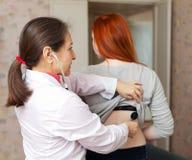 Muchacha de examen del doctor de sexo femenino con el estetoscopio Fotografía de archivo libre de regalías