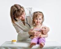 Muchacha de examen del niño del doctor Imagenes de archivo
