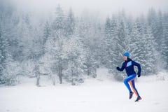 Muchacha de funcionamiento del rastro en nieve en montañas del invierno fotos de archivo libres de regalías