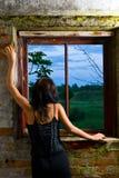 Muchacha de Goth que mira hacia fuera la ventana Imágenes de archivo libres de regalías
