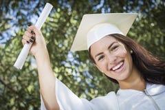Muchacha de graduación de la raza mixta en casquillo y vestido con el diploma Foto de archivo libre de regalías