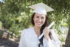 Muchacha de graduación de la raza mixta en casquillo y vestido con el diploma Fotos de archivo