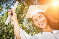 Muchacha de graduación de la raza mixta en casquillo y vestido con el diploma Fotos de archivo libres de regalías