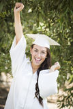 Muchacha de graduación feliz de la raza mixta en casquillo y vestido Fotos de archivo