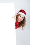 Muchacha de griterío en vestido rojo en un sombrero de la Navidad que sostiene banderas Imágenes de archivo libres de regalías