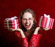 Muchacha de griterío feliz en vestido rojo con dos cajas de regalo Foto de archivo