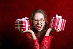 Muchacha de griterío feliz en vestido rojo con dos cajas de regalo Fotos de archivo