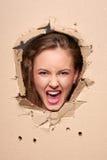 Muchacha de griterío que mira furtivamente a través del agujero en papel Imagenes de archivo