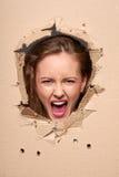 Muchacha de griterío que mira furtivamente a través del agujero en papel Fotos de archivo libres de regalías