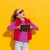 Muchacha de grito que muestra una tableta digital Imagen de archivo libre de regalías