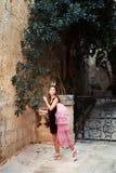Muchacha de hadas de la princesa en libra y corona que caminan a través del jardín del castillo antiguo de la ciudad imagen de archivo libre de regalías