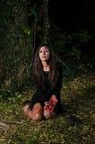 Muchacha de Halloween de la mujer con sangre en el bosque en la noche Imágenes de archivo libres de regalías