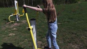 Muchacha de Ittle que hace actividades físicas en la máquina del escalonamiento en al aire libre metrajes