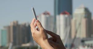 muchacha de 4k A que usa un smartphone contra el fondo moderno del edificio del negocio almacen de metraje de vídeo