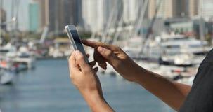 muchacha de 4k A que usa un smartphone en la playa, el yate y la navegación en el puerto almacen de video