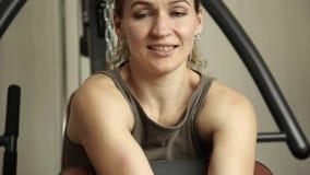 Muchacha de la aptitud con las pesas de gimnasia que hacen ejercicios en el gimnasio almacen de metraje de vídeo