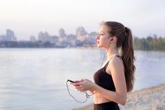 Muchacha de la aptitud en el río que escucha la música en el teléfono celular Foto de archivo libre de regalías