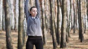 Muchacha de la aptitud en los ejercicios de práctica de las morenitas del bosque en la trayectoria metrajes