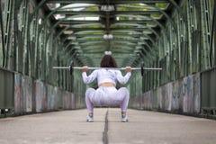 Muchacha de la aptitud que ejercita con pesa de gimnasia en la calle fotografía de archivo