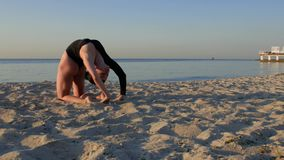 Muchacha de la aptitud que hace asana de la yoga en la arena cerca del mar o del océano Muchacha en el mono negro que practica y