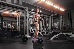 Muchacha de la aptitud que hace ejercicio con pesas de gimnasia en el gimnasio Fotos de archivo