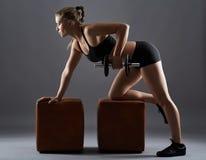 Muchacha de la aptitud que hace filas de la pesa de gimnasia Fotos de archivo