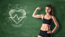 Muchacha de la aptitud que muestra su bíceps en el fondo de una pizarra con garabatos de derrota exhaustos del corazón y del depo Imágenes de archivo libres de regalías