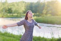 Muchacha de la belleza al aire libre que disfruta de la naturaleza, aumentando las manos sueño Foto de archivo