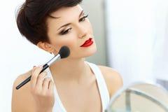 Muchacha de la belleza con el cepillo del maquillaje. Natural compense a la mujer morena con los labios rojos. Foto de archivo libre de regalías