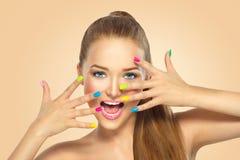 Muchacha de la belleza con el esmalte de uñas colorido Imagenes de archivo