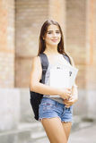 Muchacha de la belleza con el goind del bolso a estudiar en escuela o universidad Imagen de archivo