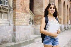 Muchacha de la belleza con el goind del bolso a estudiar en escuela o universidad Foto de archivo
