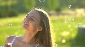 Muchacha de la belleza con el jabón de las burbujas del pelo que sopla largo en naturaleza del parque de la hierba verde Mujer he almacen de video