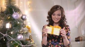 Muchacha de la belleza con la caja de regalo de la Navidad El conseguir feliz de la mujer linda joven presente almacen de video