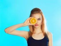 Muchacha de la belleza con la fruta anaranjada Fotos de archivo libres de regalías