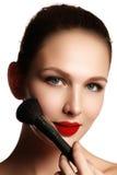 Muchacha de la belleza con los cepillos del maquillaje Natural compense la morenita Wo fotos de archivo