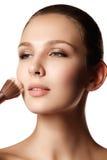 Muchacha de la belleza con los cepillos del maquillaje Natural compense la morenita Wo foto de archivo