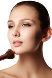 Muchacha de la belleza con los cepillos del maquillaje Natural compense la morenita Wo imágenes de archivo libres de regalías