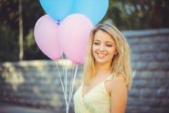 Muchacha de la belleza con los globos coloridos que ríe en una calle de la ciudad Mujer joven feliz hermosa en un día brillante s fotografía de archivo libre de regalías