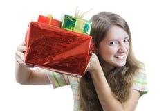 Muchacha de la belleza con los regalos de la Navidad sobre blanco Imagen de archivo