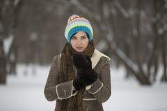 Muchacha de la belleza en parque escarchado del invierno outdoors Copos de nieve del vuelo Foto de archivo libre de regalías