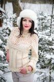 Muchacha de la belleza en suéter de lana caliente debajo de árboles nevados Foto de archivo libre de regalías