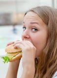 Muchacha de la belleza que come la hamburguesa Imagenes de archivo