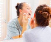 Muchacha de la belleza que limpia su cara con los cojines de algodón Imagen de archivo libre de regalías