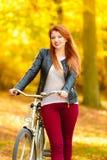 Muchacha de la belleza que se relaja en parque del otoño con la bicicleta, al aire libre Foto de archivo libre de regalías