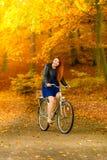 Muchacha de la belleza que se relaja en parque del otoño con la bicicleta, al aire libre Imagen de archivo
