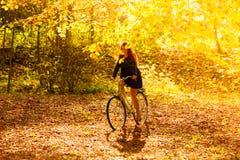 Muchacha de la belleza que se relaja en parque del otoño con la bicicleta, al aire libre Fotografía de archivo