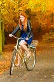 Muchacha de la belleza que se relaja en parque del otoño con la bicicleta, al aire libre Foto de archivo