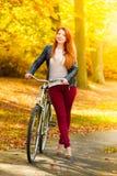 Muchacha de la belleza que se relaja en parque del otoño con la bicicleta, al aire libre Fotografía de archivo libre de regalías